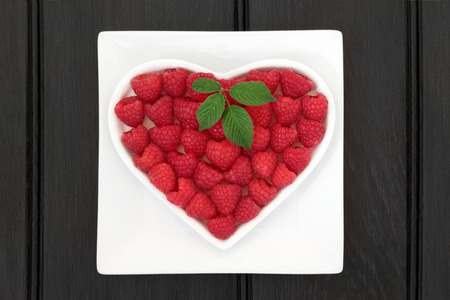 super fruit: Raspberry super food fruit in a heart shaped bowl on a white square dish over wooden black background.