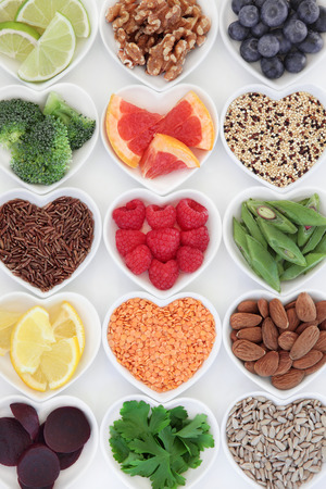 Healthy super food selection in heart shaped porcelain dishes over white background.