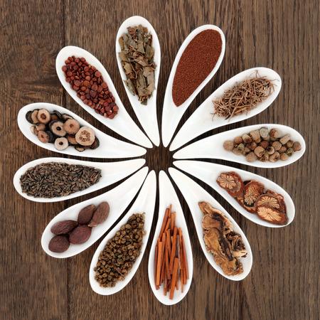 オークの背景上の磁器の皿で中国の漢方薬の選択。