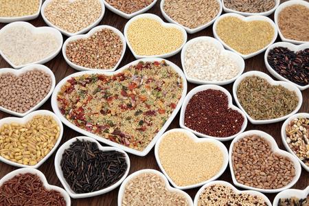 Grote granen en graan eten selectie in hartvormige porseleinen kommen over Lokta papier achtergrond. Groente couscous in grote schotel. Stockfoto