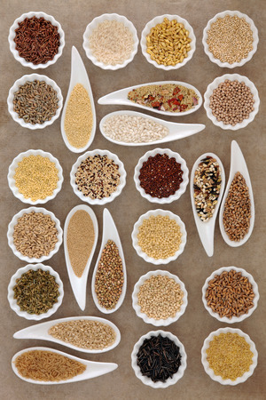wild oats: Large cereal and grain food selection in porcelain dishes over old brown paper background. Stock Photo