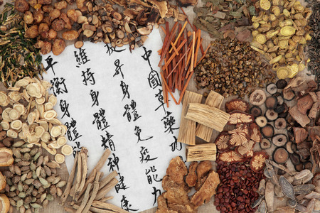 tcm: Chinese herb selection with calligraphy script. Translation describes chinese herbal medicine as increasing the bodys ability to maintain body and spirit health and balance energy.