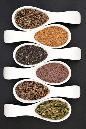 psyllium: Healthy seed food selection in white porcelain scoops over lokta grey slate background.