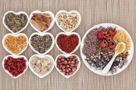 teas: Healthy herbal tea selection in heart and round shaped bowls over bamboo. Stock Photo
