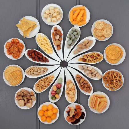 savoury: Large savoury snack selection in porcelain dishes over grey wooden background. Stock Photo
