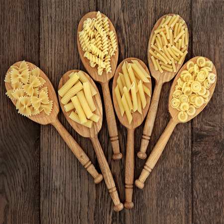 pasta: Dried pasta food selection in wooden spoons over old oak background.