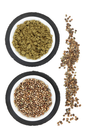hemp hemp seed: Hemp seed and powder in porcelain bowls on grey slate and loose over white background. Stock Photo