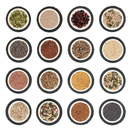 psyllium: Large seed super food selection in  porcelain bowls over slate rounds and white isolated background. Stock Photo