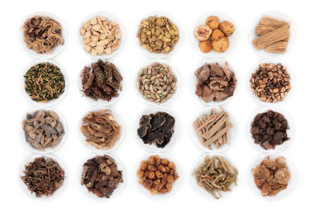 Large chinese herbal medicine selection in china bowls over white background. Stock Photo