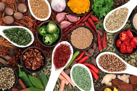 Large spice and herb collection in bowls and spoons forming an abstract background.
