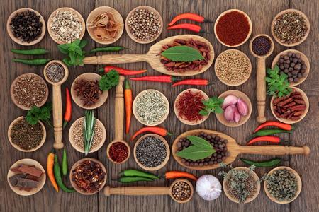 especias: Hierbas y selección de especias en cuencos de madera, cucharas y suelta sobre fondo de roble viejo. Foto de archivo