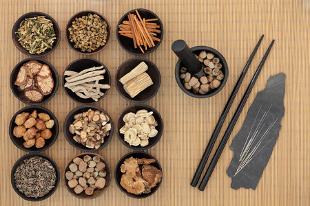 Chinese herbal medicine with acupuncture needles and chopsticks over bamboo background.