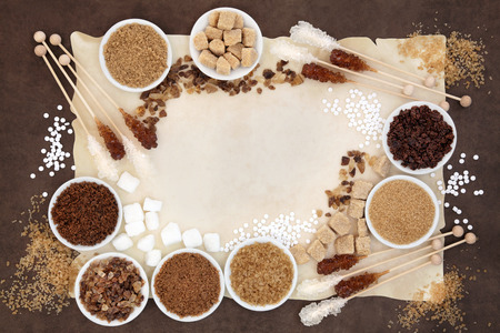molasses: Brown and white sugar with crystal lollipops over parchment and  brown paper background. Stock Photo