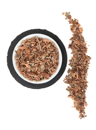 witchhazel: Witch hazel bark herb in a porcelain bowl and loose over slate round and white background.