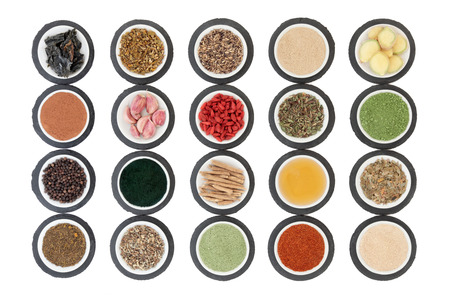 super food: Immune boosting health super food selection in porcelain dishes on slate rounds over white background.