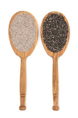 white salvia: Chia seed in oak wood spoons over white background. Salvia Hispanica. Stock Photo