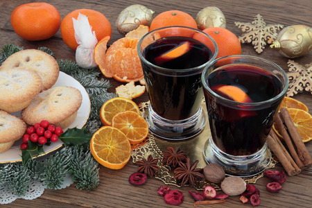 mulled: Christmas mulled wine, mince pies, spices, fruit, baubles and winter greenery over oak background.