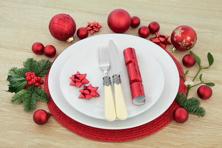 setting: Christmas dinner place setting with plates, antique cutlery, red baubles, cracker, holly, mistletoe and fir over light oak background. Stock Photo