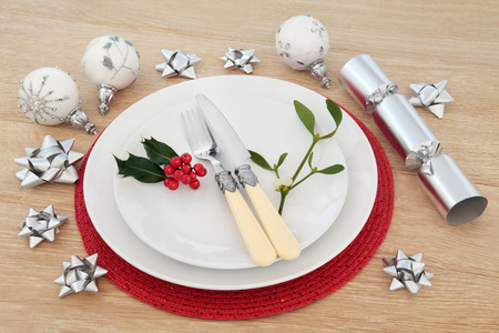 place setting: Christmas place setting with plates, cutlery, holly and mistletoe with baubles and cracker over light oak background. Stock Photo