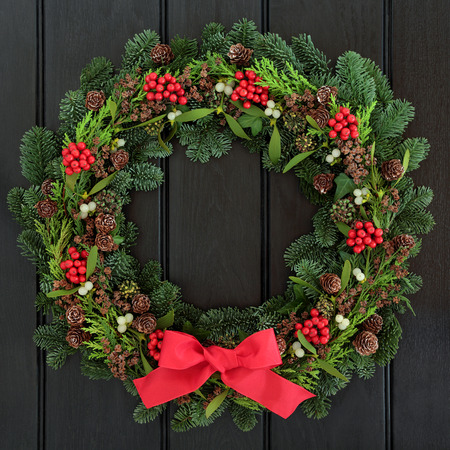 Christmas wreath with red bow, holly, mistletoe and winter greenery over dark blue oak front door background.