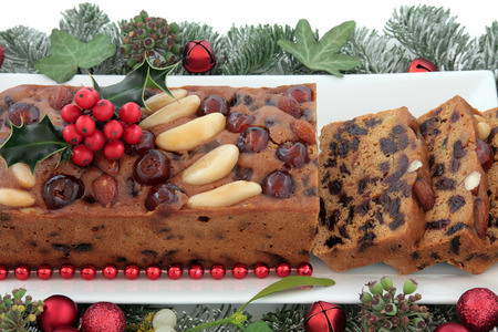 fruitcake: Genoa cake and slices with holly, red bauble christmas decorations and winter greenery over white background.