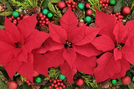 arreglo floral: Fondo de la flor Poinsettia con las decoraciones de la chuchería, el acebo, el muérdago y zonas verdes de invierno.