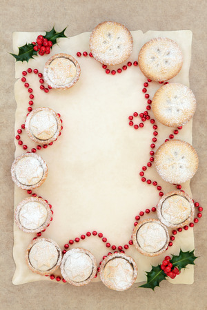 mince pie: Abstract christmas background border with mince pie cakes, holly and red bead decoration on parchment and old grunge paper.