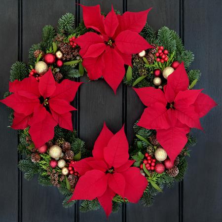 flor de pascua: Poinsettia corona de flores sobre la madera de roble oscuro fondo puerta principal.