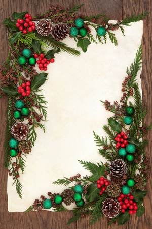 christmas ivy: Christmas background border with green bauble decorations, holly, ivy and winter greenery on old parchment paper over oak.