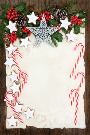 old fashioned christmas: Christmas abstract background border with gingerbread biscuits and candy canes, holly and winter greenery  on parchment paper over old oak wood. Stock Photo