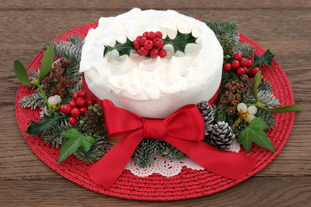 fruitcake: Traditional christmas cake with holly, mistletoe and winter greenery over oak background. Stock Photo