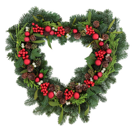 Heart shaped christmas wreath with red bauble decorations, holly, mistletoe, ivy and winter greenery over white background.