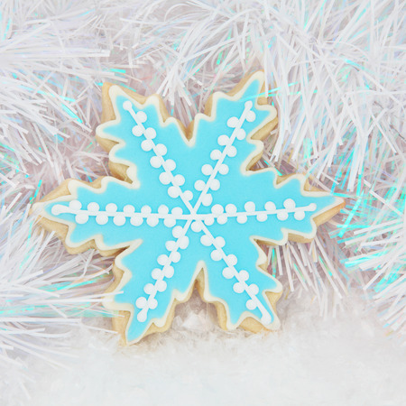 sugar cookie: Christmas gingerbread snowflake biscuit over snow and decorative background. Stock Photo