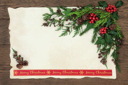 old fashioned: Background border with merry christmas ribbon, holly, ivy, fir and pine cones on parchment paper over old oak wood. Stock Photo