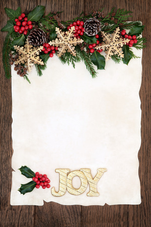 christmas ivy: Christmas background border with gold joy sign and snowflake bauble decorations, holly, ivy and winter greenery on parchment paper over old oak wood.