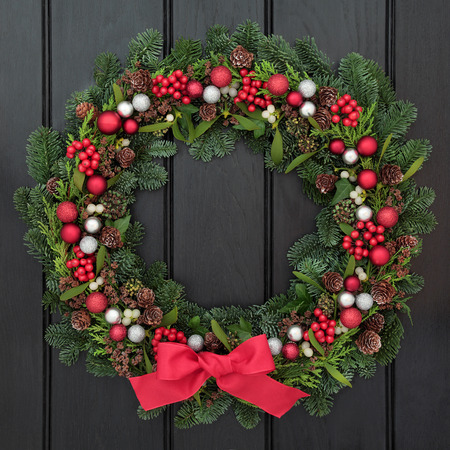 welcome symbol: Christmas wreath with red bow and bauble decorations, holly, mistletoe and winter greenery over dark blue oak front door background.