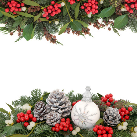 christmas baubles: Christmas background border with snowflake bauble, holly, mistletoe, fir, snow covered pine cones and traditional greenery over white.