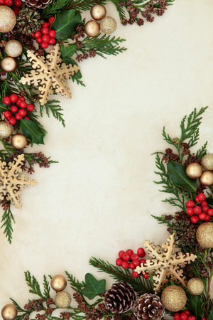 red snowflake background: Christmas abstract background border with gold snowflake and bauble decorations, holly, fir and cedar cypress greenery.
