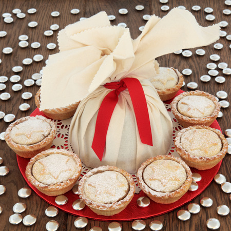 doiley: Christmas pudding in a muslin bag with mince pies and small gold sweets over oak background.