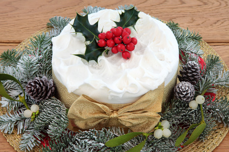 cakes and pastries: Traditional christmas cake with holly, mistletoe and winter greenery over oak background. Stock Photo
