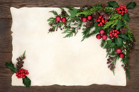 Christmas background floral border with red bauble decorations, holly, ivy, fir, cedar cypress and pine cones on parchment paper over old oak wood. Archivio Fotografico