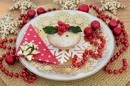 gold christmas decorations: Mince pie and holly with christmas bauble and snowflake decorations over gold background.