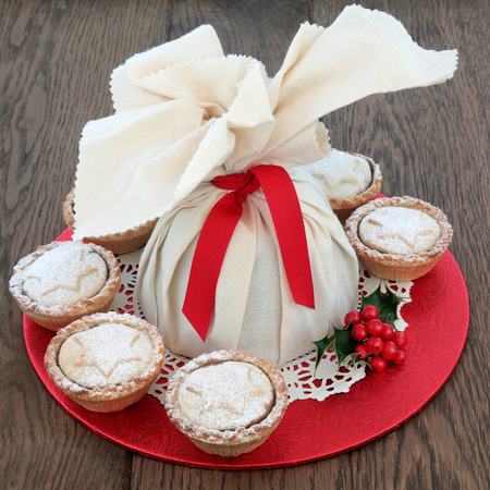 doiley: Christmas pudding in a muslin bag with mince pies and holly over oak background. Stock Photo