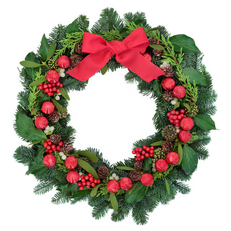 pine wreath: Christmas wreath with red bauble decorations and bow, holly, ivy, mistletoe and winter greenery over white background. Stock Photo