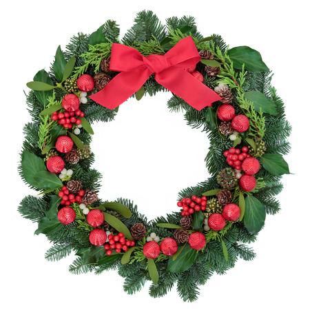 Kerst krans met rode snuisterijdecoratie en boog, hulst, klimop, maretak en winter groen op een witte achtergrond.