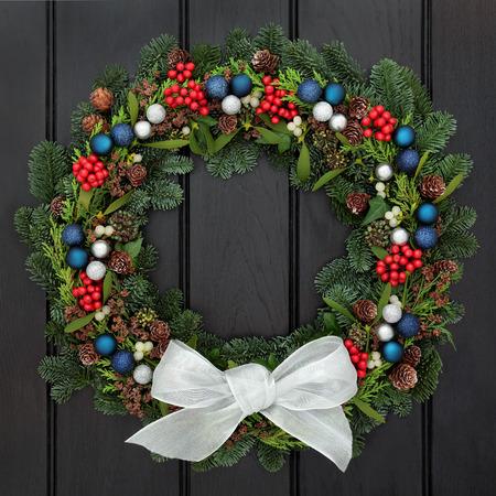 mo�o blanco: Corona de Navidad con lazo blanco, Decoraciones de la chucher�a, acebo, mu�rdago, pi�as de pino y el abeto azul sobre fondo de roble oscuro. Foto de archivo