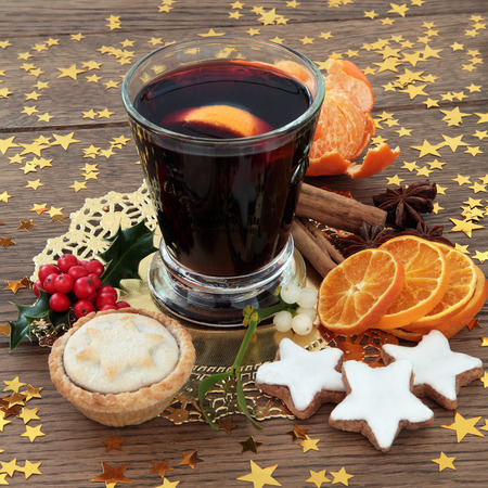 mulled: Christmas mulled wine with gingerbread biscuits, mince pie, spices, fruit, holly and mistletie over oak background.