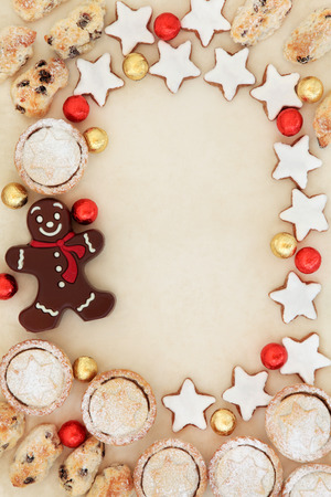 cookies: Abstract christmas background border with stollen, mince pie cakes, gingerbread biscuits and foil wrapped chocolate balls  on parchment paper.