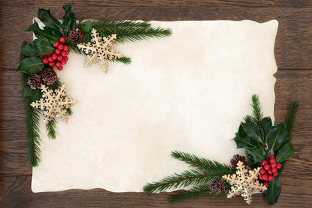 christmas ivy: Christmas abstract background border with snowflake bauble decorations, holly, ivy and fir on parchment paper over old oak wood.