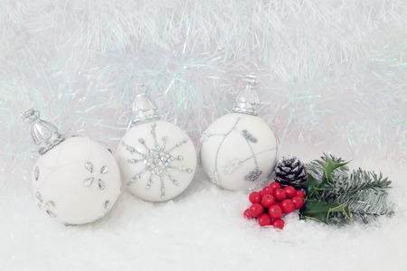 christmas winter: Christmas white bauble decorations with holly and fir on snow with decorative tinsel  background.